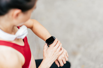 Cropped portrait of asian woman in sportswear looking at smartwatch on her wrist while having a rest after workout session. Horizontal shot. High angle