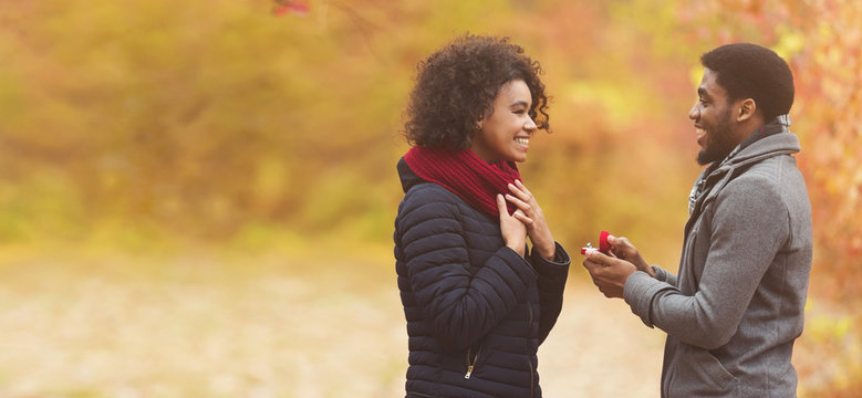 Romantic man proposing to woman in autumn park