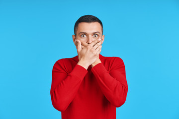Shocked man covering mouth with hands over blue background