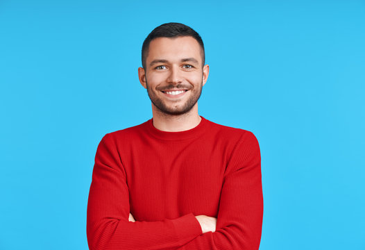 Happy smiling handsome man with crossed arms looking to camera over blue background