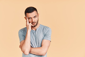 Young thoughtful man thinking and looking to camera with copy space, isolated on studio background