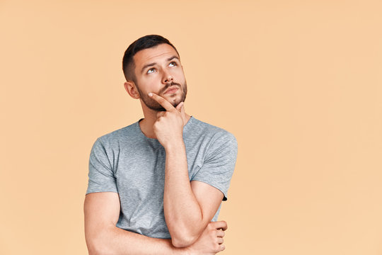 Young thoughtful man thinking and looking aside on copy space isolated on yellow background
