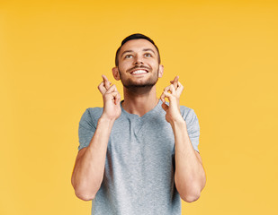 Young man making a wish and ask for good luck with crossed fingers isolated on yellow background