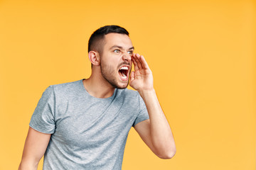 Young angry man shouting and screaming loud to side with hand on mouth and copy space for text over yellow background