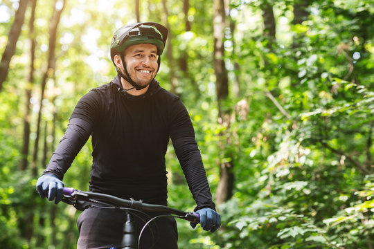 Joyful male bicyclist cycling in mountain forest