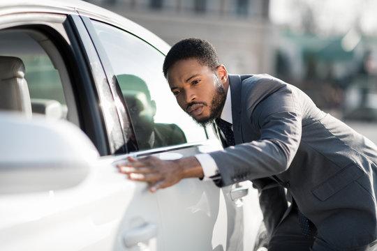 The final check. Afro man examining new car at dealership