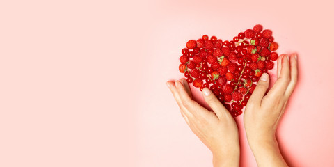 Female hands and red berries in the shape of a heart on a pink background.