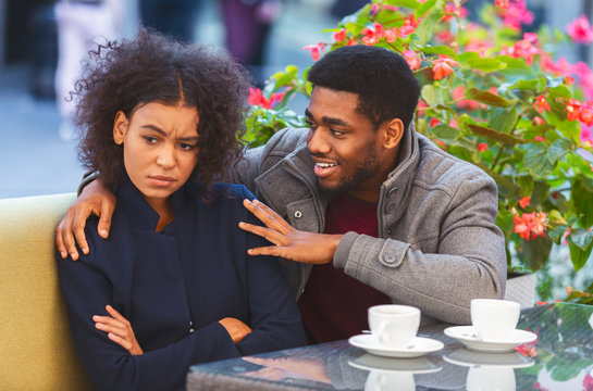 Cheerful black guy trying to cheer up his angry girlfriend