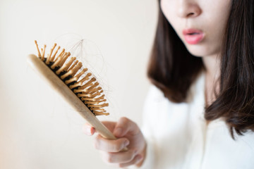 Young asian woman worried about hair loss after brushing her hair with comb. Hair problems and health care concept. Close up.