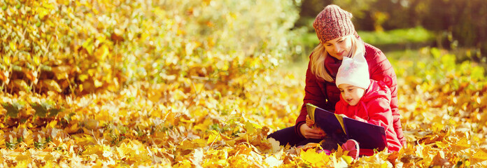 mother teaching daughter in autumn park, Mother teaching daughter to read. Fototapete