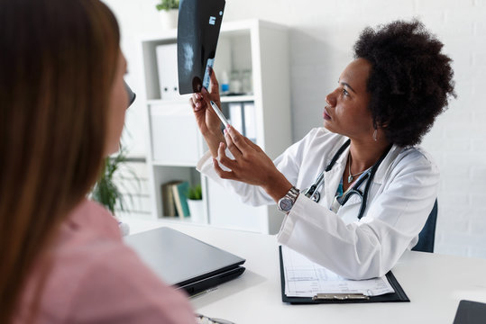 A female doctor sits at her desk and talks to a female patient while looking at her mamogram. Brest cancer