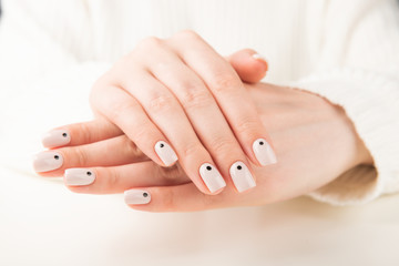 Foto op Canvas Manicure hand with beige manicure with dots nail design..