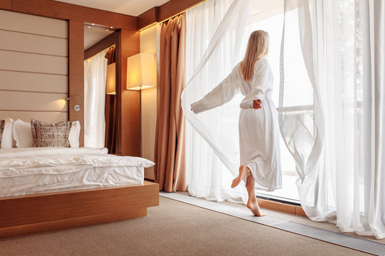 Joyful emotional young beautiful woman in white bathrobe happily opens the curtains of her window in the bedroom on a sunny summer morning. The concept of starting a new day and fulfilling your plans