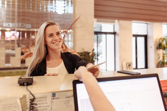 Smiling charming young woman gets a bank loan after successful approval. Pretty woman receives hotel room keys during check-in during business trip. Nice girl receives money transfer at post office