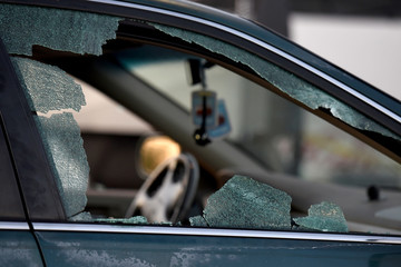 A car with a broken window is seen at a grocery store parking lot following Saturday's shooting in Odessa, Texas