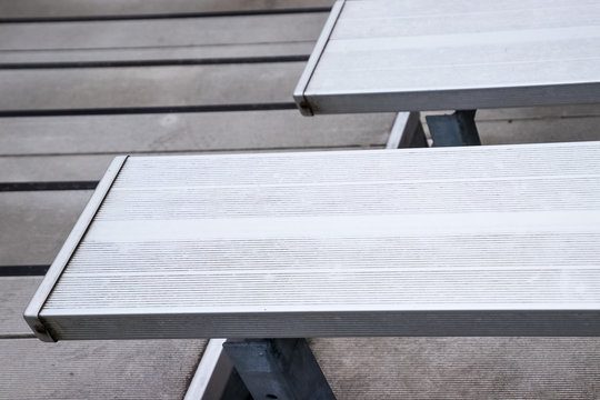 Empty metal bleachers seats in football, soccer or baseball stadium during local game