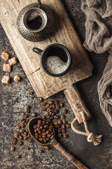 Wall Mural - Coffee on wooden board with coffee beans on dark textured background. Top view with copy space. Background with free text space.