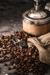Wall Mural - Coffee beans with coffee grinder on dark textured background.