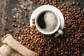 Fototapete - Coffee cup and coffee beans on dark stone background..