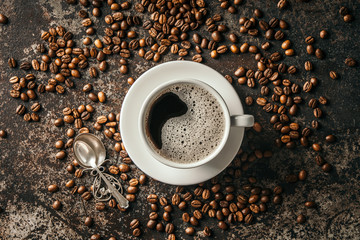 Coffee cup and coffee beans on dark stone background. .