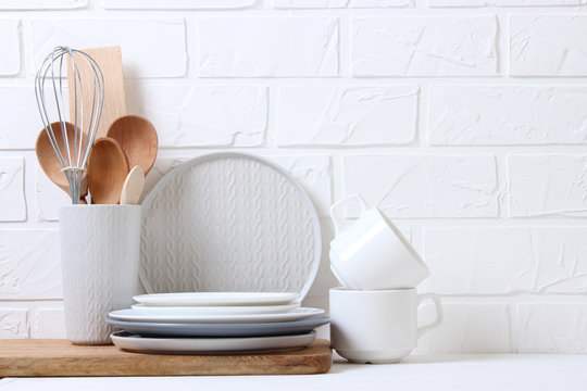 A set of dishes and kitchen utensils on a colored background.