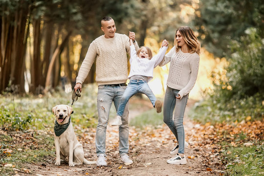 Happy beautiful family with dog labrador is having fun together walking the in park.