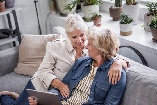 Mature lesbian couple looking at digital tablet together on sofa