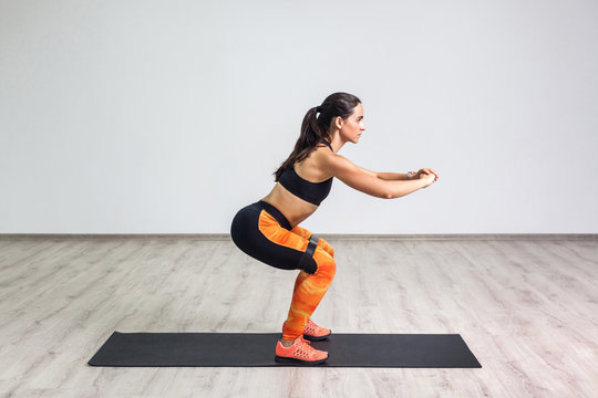 Side view portrait of young sporty healthy beautiful woman in black top and orange leggings doing squatting with elastic resistance band. Isolated, white wall, indoor, workout concept, looking away