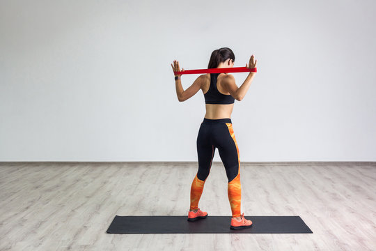 Full length back side portrait of sporty woman wearing in black top and orange leggings performs exercises for the muscles of back and hands, workout with resistance band on white background. Indoor