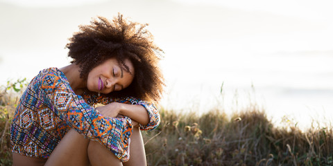 Pretty afro hairstyle woman relaxing on summer trip to the coast. Asturias, Spain.