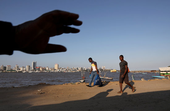 A hand of a local is seen as people returning from work walk along the beach, with the city skyline in the background, ahead of Pope Francis's visit to Maputo