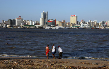 Locals take a walk along the beach, with the city skyline in the background, ahead of Pope Francis's visit to Maputo