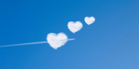 Flugzeug fliegt durch eine Wolke in Herzform