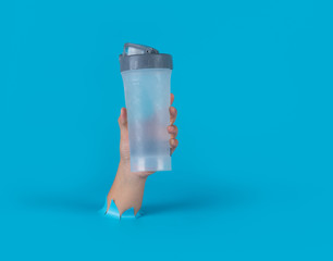 Hand holding plastic sport water bottle through the torn blue plastic background