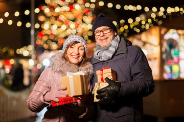 love, winter holidays and people concept - happy senior couple with gift at christmas market on town hall square in tallinn, estonia