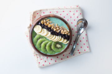 healthy spirulina smoothie bowl with granola, currant, bananas and kiwi