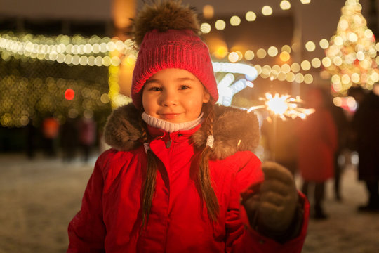 holidays, childhood and people concept - happy little girl with sparkler at christmas market in winter evening