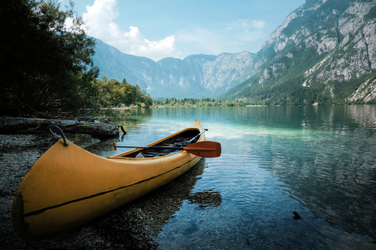 canoeing in the lake bohinj on a summer day, background alps mountains.