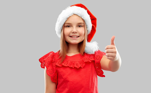 christmas, childhood and holidays concept - smiling girl posing in snata helper hat showing thumbs up over grey background