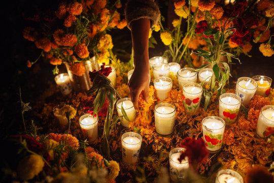 Una mujer coloca pétalos de flores en una ofrenda durante el Día de Muertos en Tzintzuntzan, México