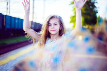 Portrait of a beautiful little girl, throwing a scarf, with gorgeous hair.