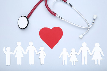 Family figures with red heart and stethoscope on grey background
