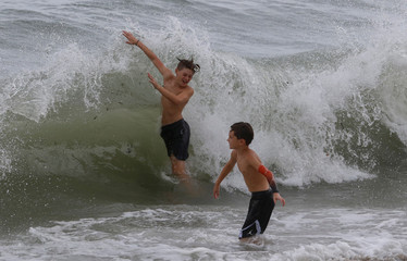 Children play in the surf ahead of the arrival of Hurricane Dorian in Boca Raton