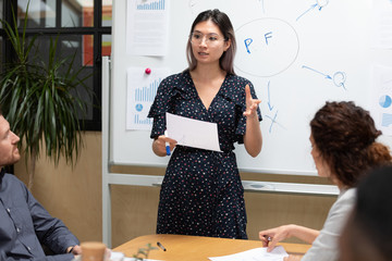 Asian businesswoman coach speaker give business presentation on whiteboard