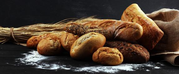 Fototapeten Brot Assortment of baked bread and bread rolls on black table background