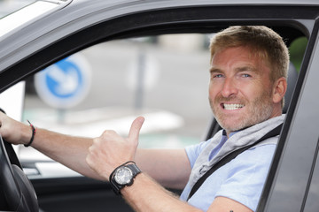 handsome man in a car with thumbs up