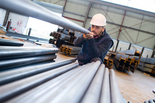 a builder inspecting steel tubes
