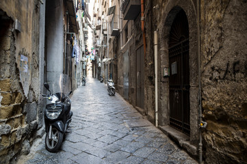 Foto auf Acrylglas Schmale Gasse Scenic view of typical narrow alleyway lined with scooters and laundry lines in the Medieval Centro Storico of Naples, Italy
