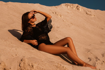 Outdoor full-length portrait of young beautiful woman with luxury tanned body wearing boho style black crochet top, swimwear, stylish sunglasses, posing on sand, at sunset. Copy, empty space for text