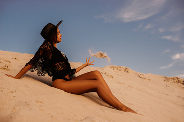 Outdoor full-length portrait of young beautiful woman with luxury tanned body wearing boho style crochet top, swimwear, hat, playing with sand, posing on beach, at sunset. Copy, empty space for text